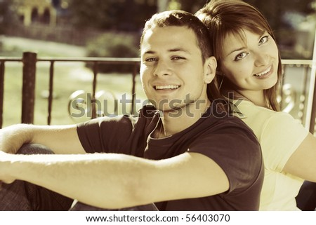 Portrait of couple on the bench in the park - stock photo