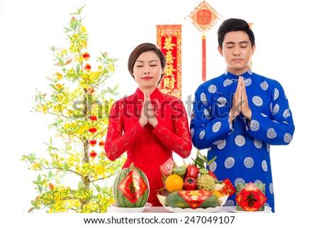 Portrait of couple praying before Vietnamese New Year celebration - stock photo