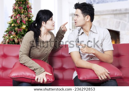 Portrait of couple quarreling, pointing, and blaming each other at home in christmas day - stock photo
