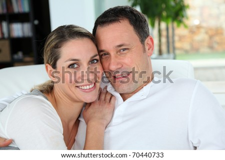 Portrait of couple relaxing at home in sofa - stock photo