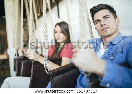 Portrait of couple sitting in swings posing - stock photo