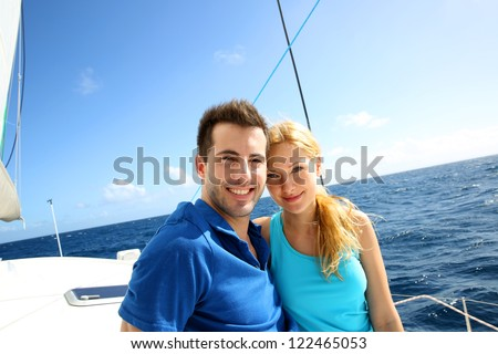 Portrait of couple sitting on the top of sailing boat - stock photo