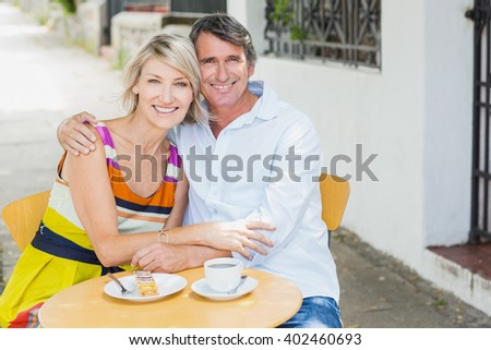 Portrait of couple sitting with arm around at cafe - stock photo