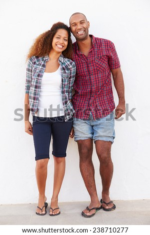 Portrait Of Couple Standing Outdoors Against White Wall - stock photo
