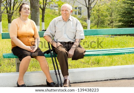 Portrait of couple talking and sitting on the park bench - stock photo