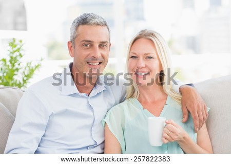 Portrait of couple with coffee cup sitting on sofa at home - stock photo