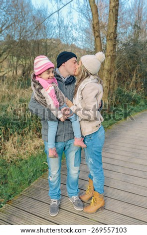 Portrait of couple with her happy little daughter kissing over a forest background. Family love concept. - stock photo