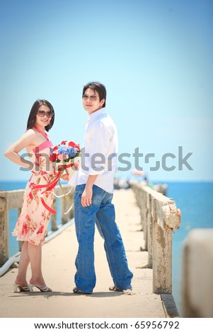 portrait of couples at pier on the beach - stock photo