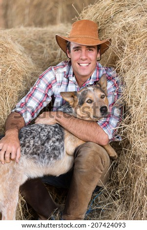 portrait of cowboy with his dog sitting on hay - stock photo