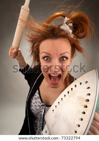 Portrait of crazy housewife with steam iron and roller - stock photo