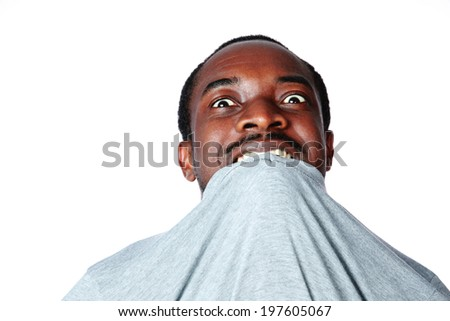 Portrait of crazy young african man biting his t-shirt over white background - stock photo