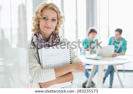 Portrait of creative businesswoman holding files with colleagues working in background at office - stock photo