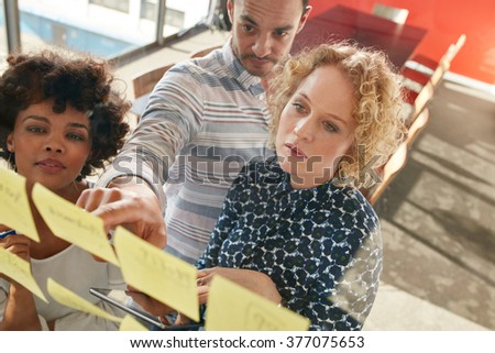 Portrait of creative professionals looking over a postit note wall and brainstorming. Young man and women standing at the office behind glass wall with sticky notes. - stock photo