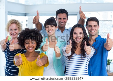 Portrait of creative team gesturing thumbs up in the office - stock photo