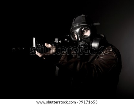 portrait of criminal with m4 rifle and gas mask - stock photo