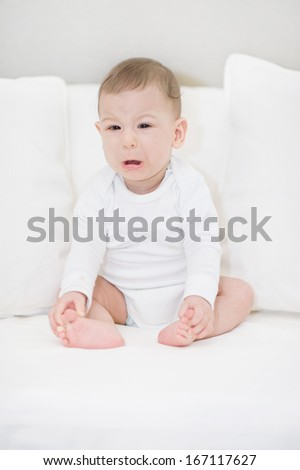 Portrait of crying baby boy in white. Little Angel  - stock photo