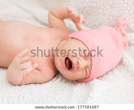 Portrait of crying newborn baby girl with pink hat. - stock photo