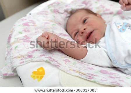 Portrait of crying newborn baby on the bed at home - stock photo