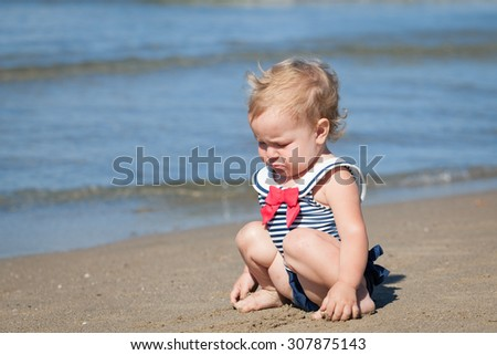 Portrait of crying sad baby girl in swimsuit on beach - stock photo