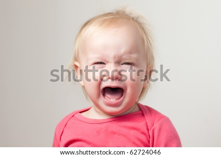 Portrait of crying young baby sit on chair - stock photo