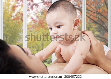 Portrait of curious male infant lying on the father chest and staring the father face, shot with autumn background on the window - stock photo