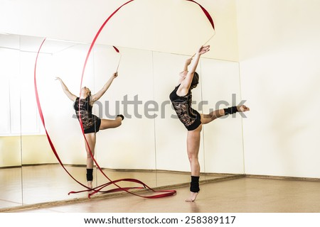 Portrait of cut Pretty rhythmic gymnast girl exercising with red ribbon with reflection on mirror yellow wall background Caucasian Woman in sexy lace transparent suit, woolen golfs stand on one leg - stock photo