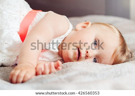 Portrait of cute adorable blonde Caucasian smiling baby child girl with blue eyes in white dress lying on bed looking in camera dreaming, fairy tale sun light leak ray beam from above behind - stock photo