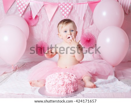 Portrait of cute adorable Caucasian baby girl with blue eyes in pink tutu skirt celebrating her first birthday with gourmet cake and balloons looking in camera, cake smash first year concept - stock photo