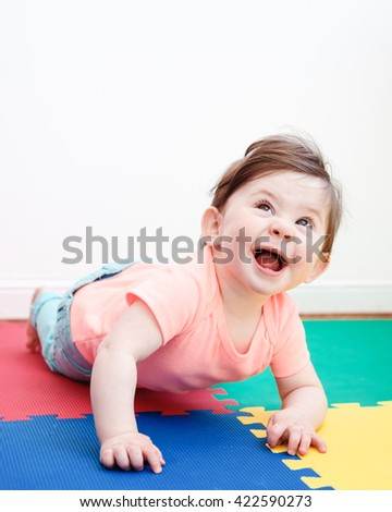 Portrait of cute adorable Caucasian smiling baby boy girl lying on floor in kids room looking in camera, natural window light, lifestyle - stock photo