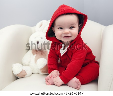 Portrait of cute adorable Caucasian smiling laughing baby boy girl with black brown eyes in red hoodie shirt sitting in chair with toy looking directly in camera - stock photo
