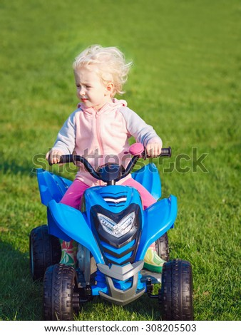 Portrait of cute adorable happy little blond Caucasian boy girl child driving blue electric car in park outside on sunny windy summer day - stock photo