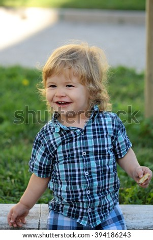 Portrait of cute adorable small happy smiling boy child with blonde hair in stylish blue checkered shirt outdoor on summer green grass background, vertical picture - stock photo
