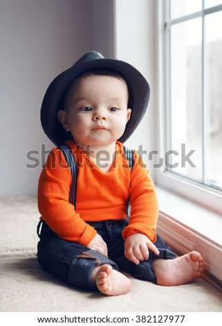 Portrait of cute adorable stylish Caucasian baby boy with black eyes in hat, orange shirt onesie, jeans with suspenders barefoot sitting on windowsill looking away, natural window light, lifestyle - stock photo