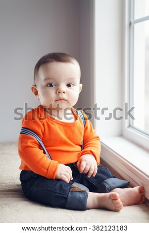 Portrait of cute adorable stylish Caucasian baby boy with black eyes in orange red shirt onesie, jeans with suspenders barefoot sitting on windowsill looking in camera, natural window light, lifestyle - stock photo