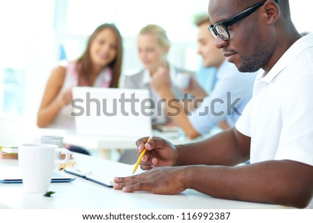 Portrait of cute African guy working with his partners on background - stock photo