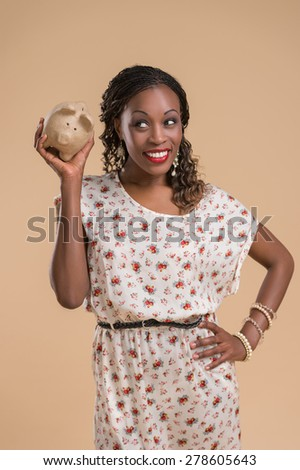 Portrait of cute african woman posing - holding piggy moneybox - stock photo