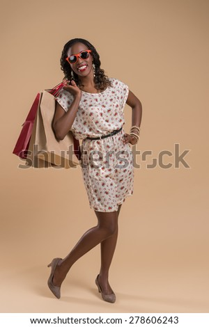 Portrait of cute african woman posing - shopping with bags and sunglasses - stock photo