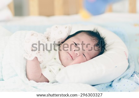 Portrait of cute asian baby looking on bed,vintage filter - stock photo