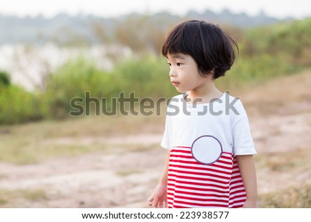 portrait of cute asian boy in the park - stock photo