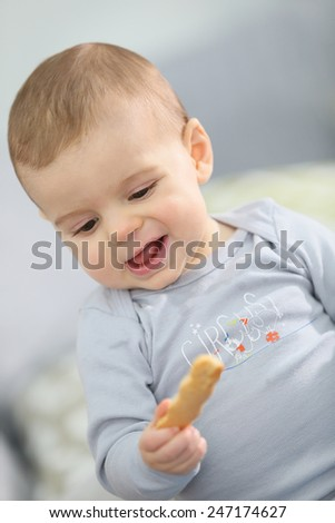 Portrait of cute baby boy eating child biscuit - stock photo
