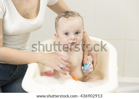 Portrait of cute baby boy having bath and playing with toys - stock photo