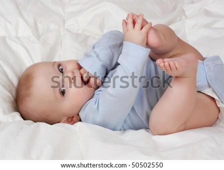 portrait of cute baby boy on white blanket - stock photo