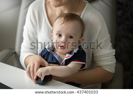 Portrait of cute baby boy sitting on mothers lap while she is working at computer - stock photo
