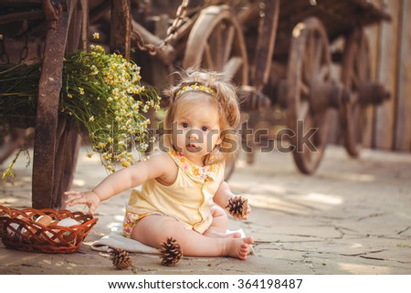 Portrait of cute baby girl resting on the farm at summer day, Beautiful child. lovely infant baby girl with happy smile. rabbit and chicken in the farm around.  - stock photo