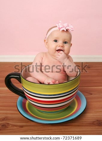 Portrait of cute baby girl sitting inside a giant tea cup or mug - stock photo