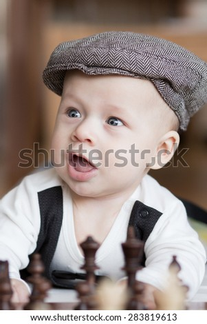 Portrait of cute baby playing chess.  - stock photo