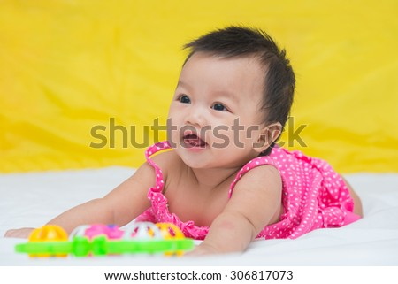 Portrait of cute baby smile girl on the bed with toy. - stock photo