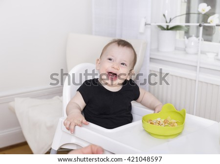 portrait of cute baby toddler sitting with dining table having a meal and laughing with open mouth and just two teeth - stock photo