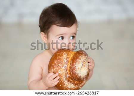 Portrait of cute baby with  bread in her hands eating - stock photo