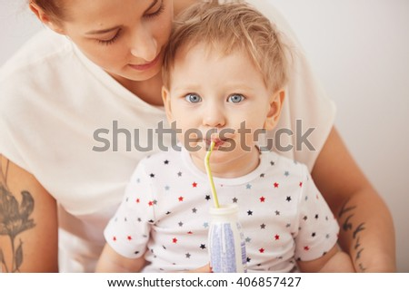 Portrait of cute blond blue-eyed baby boy looking at the camera while drinking through straw, sitting on his mother's laps in pajamas. Young beautiful woman caring for her adorable two-year old son - stock photo